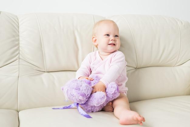 Kind, jeugd en kinderen concept - portret van charmante babymeisje op de bank