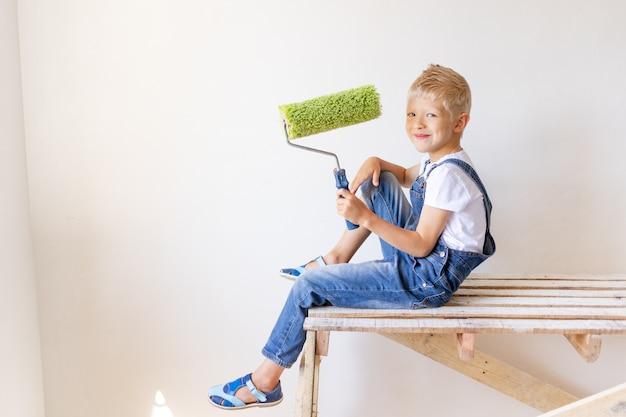 Kind jongen bouwer houdt bouwgereedschap in een appartement met witte muren, kind schildert de muren, plaats voor tekst, reparatie concept