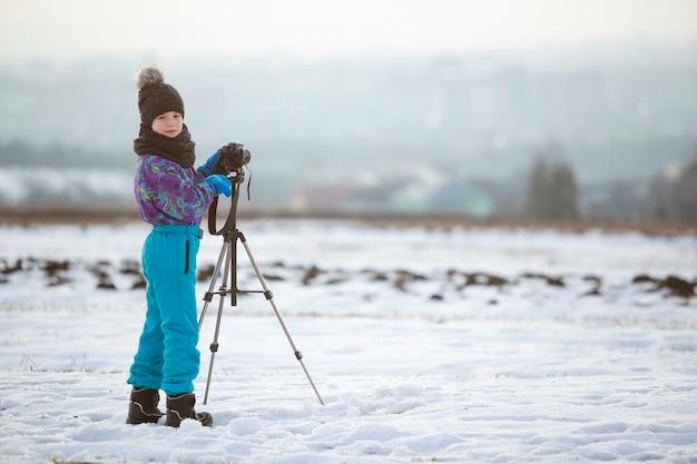 Kind jongen fotograferen buiten in de winter met fotocamera op een statief op sneeuw bedekt veld.