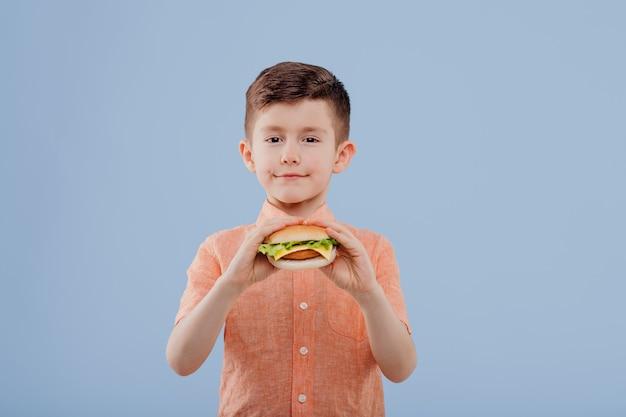 Kind jongen met boterham in de hand kijkt naar de camera geïsoleerd op blauwe achtergrond kopie ruimte