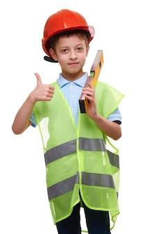 Kind jongen met constructie level vest en helm geïsoleerd op wit toont duim omhoog gebaar, toekomstige bouwvakker