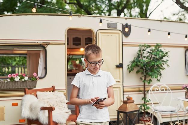 Kind jongen met een telefoon op vakantie in de zomer in de buurt van het huis op wielen