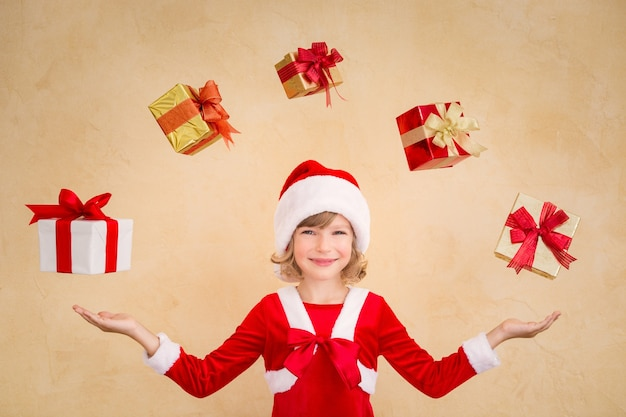 Kind jongleren met kerstcadeaudozen. kerst vakantie concept