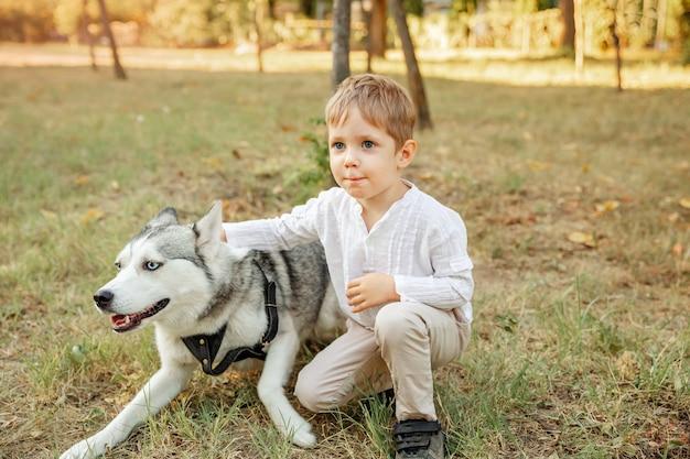 Kind kamperen met hond. mooie jonge jongen die zijn puppy koestert