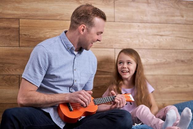 Kind kijken naar vader ukulele spelen, jonge man vader laten zien hoe te spelen op muziekinstrument