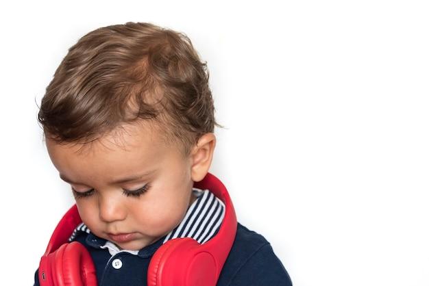 Kind kijken naar video's op mobiele telefoon met rode koptelefoon en donkerblauw shirt