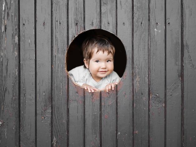 Kind kijkt door een rond gat. donkere houten muur. lacht naar de camera. plaats voor inschrijvingen. portret van gelukkig jongetje, het kind kijkt uit ronde houten raam en lacht