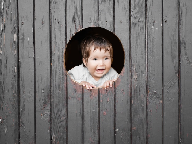 Kind kijkt door een rond gat. donkere houten muur. plaats voor inschrijvingen. portret van gelukkig jongetje, het kind kijkt uit ronde houten raam en lacht