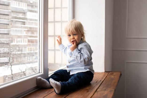 Kind kijkt uit het raam. schattige kleine blonde jongen jongen zittend op de vensterbank.