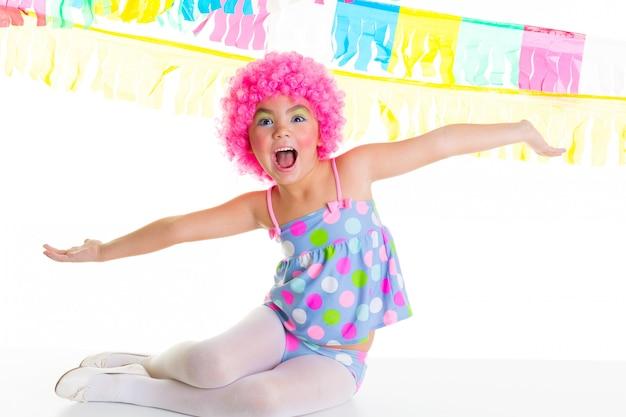 Kind kind meisje met feest clown roze pruik grappige expressie