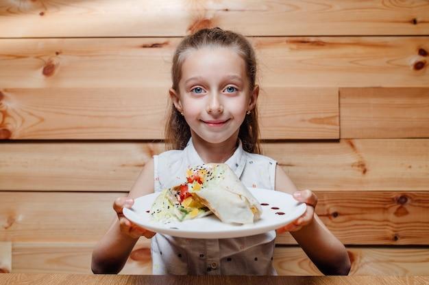 Kind klein meisje met vegetarische wrap ijsberg,