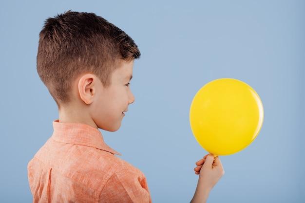 Kind. kleine jongen houdt een gele ballon vast. kijk naar de bal. profielweergave, geïsoleerd op een blauwe achtergrond, kopieer ruimte