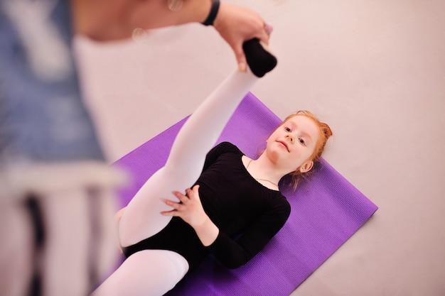 Kind - kleine schattige roodharige meisje ballerina voert uitrekkende oefeningen in balletschool