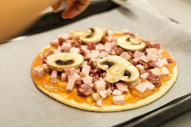 Kind kookt zelfgemaakte pizza, klein meisje maakt thuis pizza