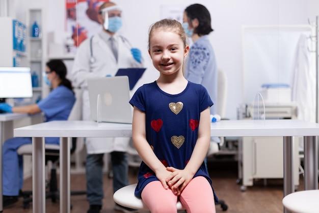 Kind lacht naar de camera tijdens medisch onderzoek op ziekenhuiskantoor. specialist in geneeskunde die consultatie van gezondheidszorgdiensten verleent, radiografische behandeling in de kliniek.