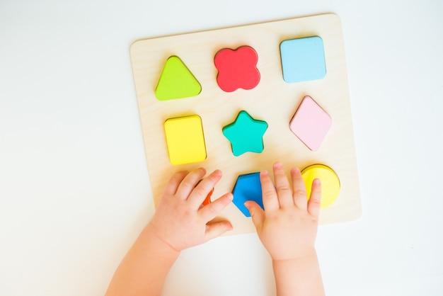 Kind leert geometrische vormen. kind dat leert om problemen op te lossen en cognitieve vaardigheden te ontwikkelen