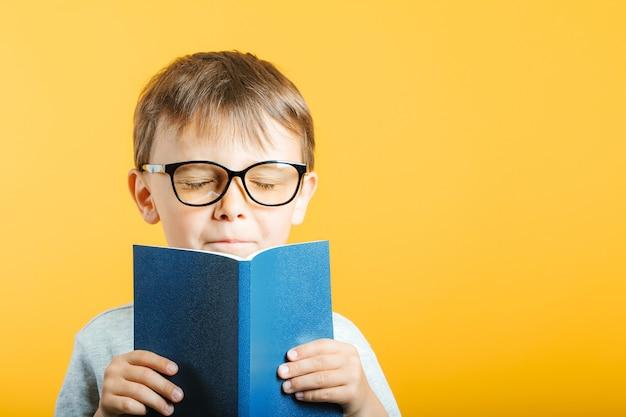 Kind leest een boek tegen een lichte muur