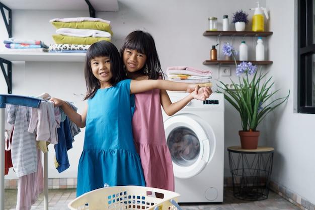 Kind leuk gelukkig klein meisje om kleren te wassen en lacht in de wasruimte Premium Foto