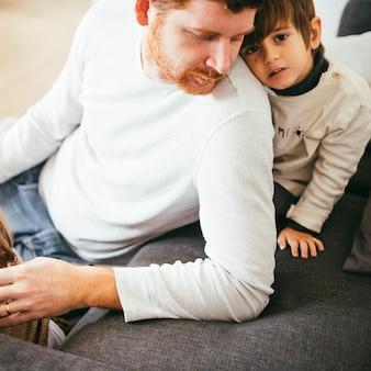 Kind leunend op de achterkant van de volwassen man
