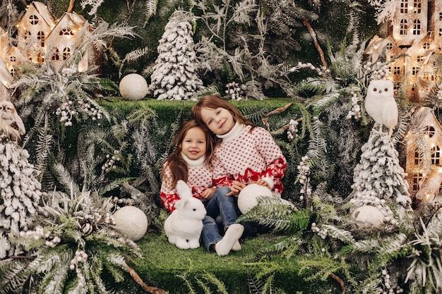 Kind leunt naar haar zus, zittend bij een speelgoedkonijn tussen de kerstbomen