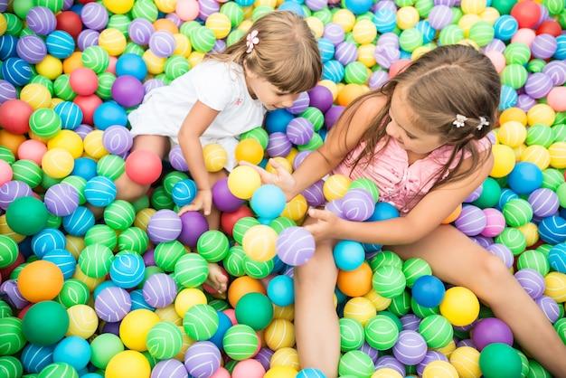 Kind liggend in zwembad met plastic ballen