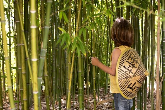 Kind loopt door een bamboebos