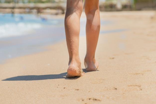 Kind loopt langs het strand en laat voetafdrukken achter in het zand