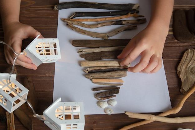 Kind maakt een kerstboomambacht met stokjes