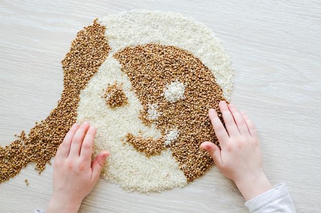 Kind maakt een toepassing van boekweit en rijst. creativiteit concept. thuis koken.