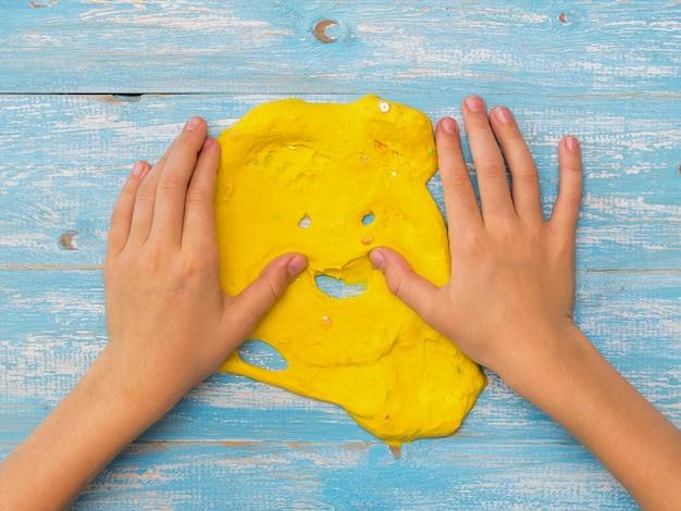 Kind maakt handen geel slijm glad op een blauwe tafel