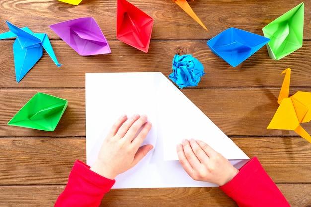 Kind maakt origami van gekleurd papier op een houten tafel
