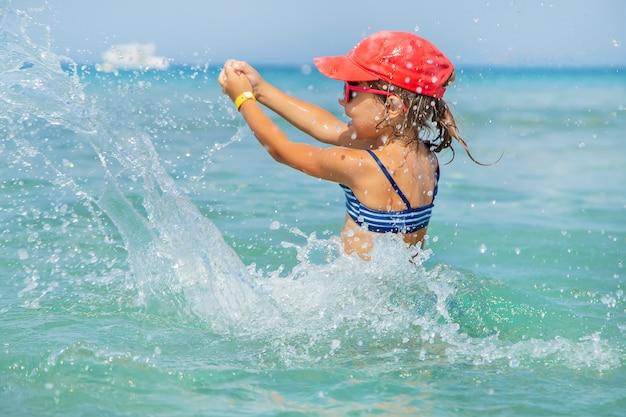 Kind maakt spray op de zee