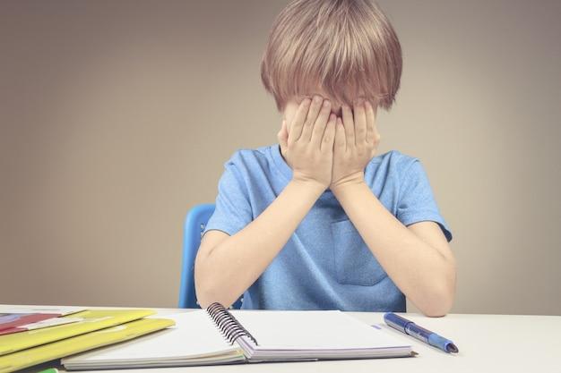 Kind maakte zijn huiswerk thuis, de jongen had er genoeg van en bedekt zijn gezicht met handen