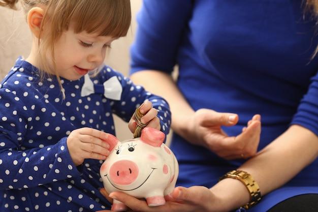 Kind meisje arm munten aanbrengend spaarpot