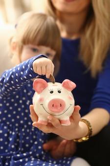 Kind meisje arm munten in spaarpot zetten