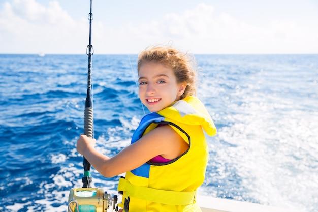 Kind meisje boot vissen trollen staaf reel en geel reddingsvest