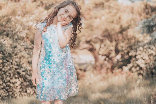 Kind meisje brunette met donker haar in een glanzende jurk in de natuur. vanille kleuring. hoge kwaliteit foto