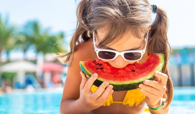 Kind meisje eet watermeloen bij het zwembad