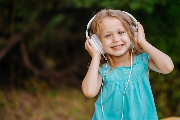 Kind meisje geniet van muziek in haar grote witte koptelefoon. een meisje buiten staan en naar muziek luisteren