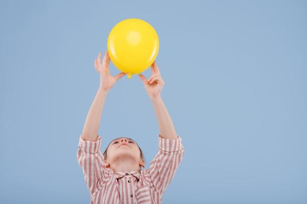 Kind meisje houdt gele ballon omhoog gekleed in gestreept shirt geïsoleerd op blauwe achtergrond kopie ruimte