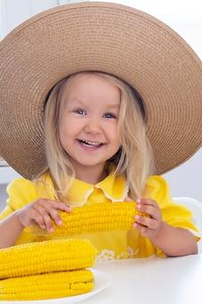 Kind meisje in een strooien hoed in gele kleren eet maïs, zomerfoto. op een lichte achtergrond. verticale foto
