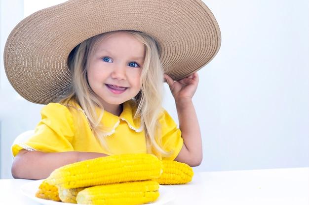 Kind meisje in een strooien hoed in gele kleren eet maïs, zomerfoto. op een lichte achtergrond