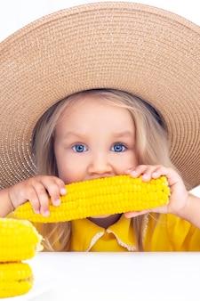 Kind meisje in een strooien hoed in gele kleren eet maïs