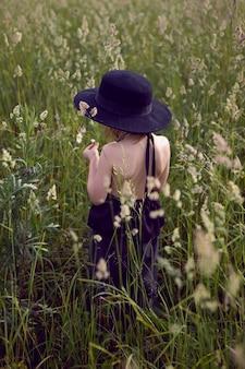 Kind meisje in een zwarte hoed en jurk staat in een veld met een gras in de zomer