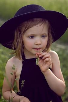 Kind meisje in een zwarte hoed en jurk staat in een veld met een gras in haar mond in de zomer
