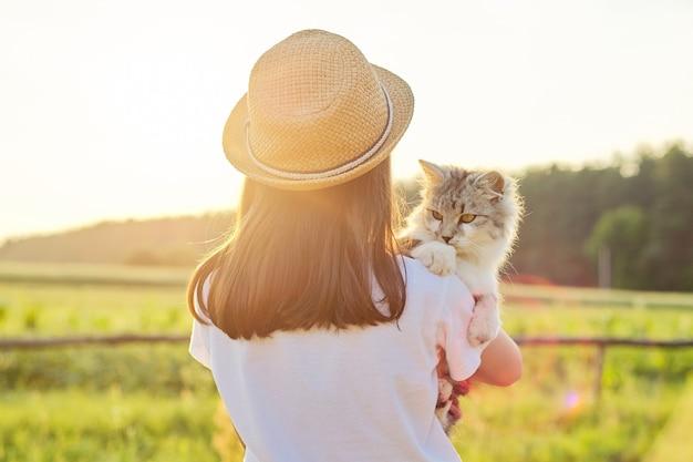 Kind meisje in hoed met grijze pluizige kat in haar armen. prachtige zonsondergang land landschap achtergrond, achteraanzicht