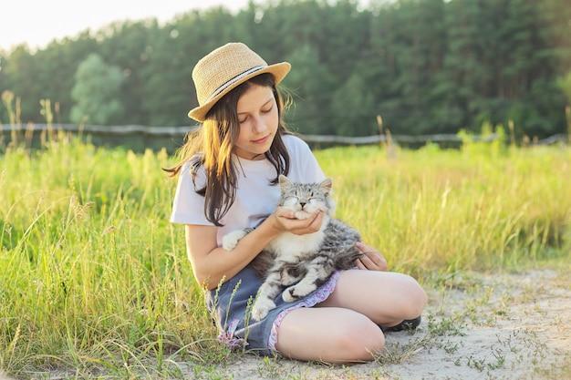 Kind meisje in hoed met grijze pluizige kat in haar armen. prachtige zonsondergang land landschap achtergrond.