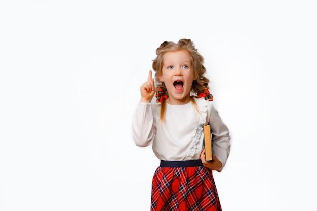 Kind meisje in schooluniform staat met boeken in haar handen toont emoties verrassing, vreugde geïsoleerd op een witte achtergrond