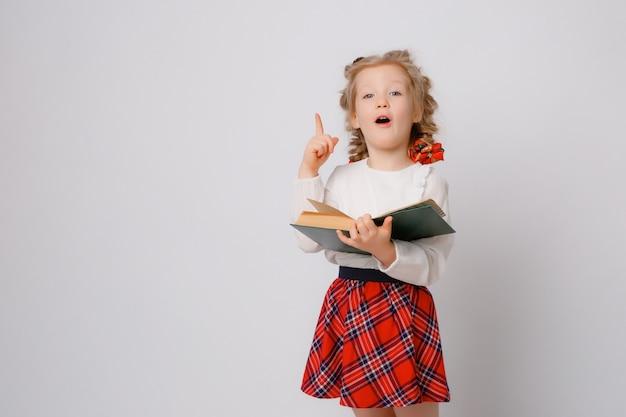 Kind meisje in schooluniform staat met boeken in haar handen toont emoties verrassing, vreugde