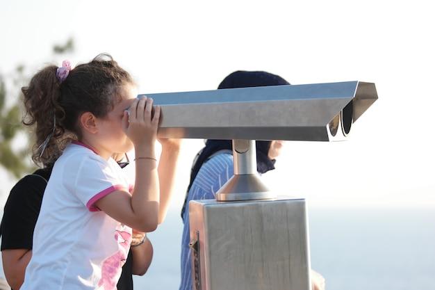 Kind meisje kijken door telescoop buitenshuis.